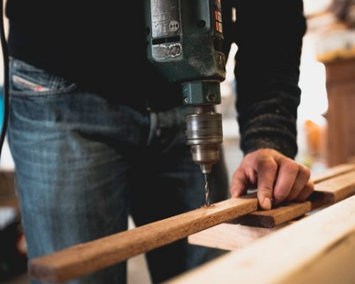man-holding-wooden-stick-while-drilling-hole-1094767